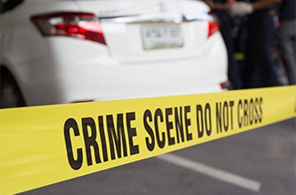 Crime Scene tape with cars in the background